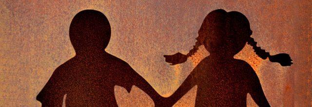 Seinään syntyvässä varjossa kaksi ihmistä pitävät toisiaan kädestä kiinni