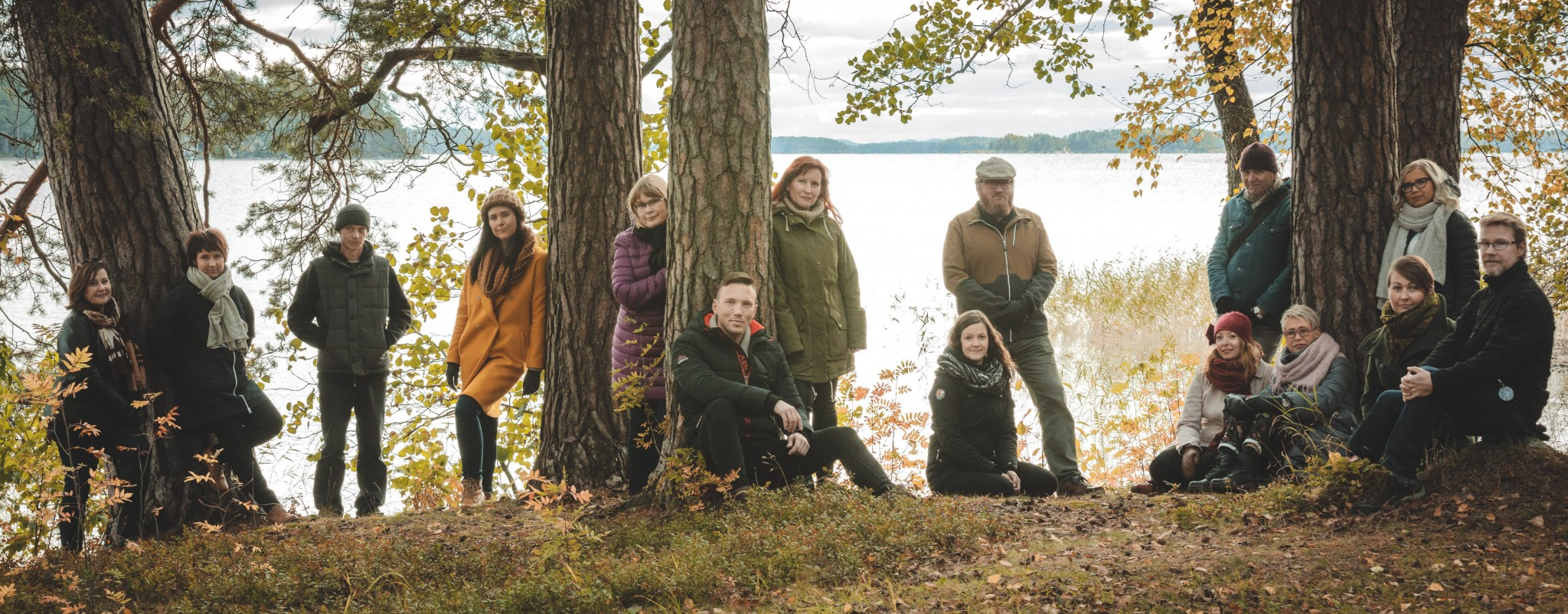 Kriisikeskuksen työntekijät kuvattuina puiden keskellä ja taustalla näkyy järvi.